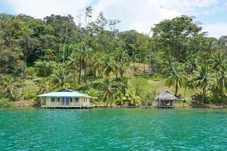 oceanfront: Oceanfront property in Central America with coconut palm trees and a house with hut over water, Caribbean coast of Panama, Bocas del Toro