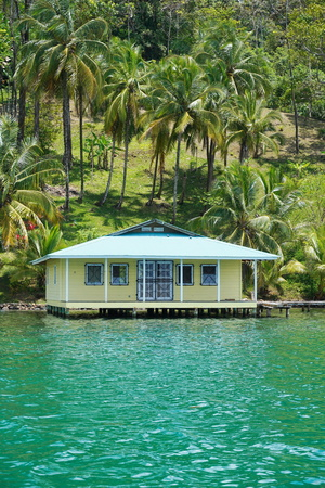 bocas del toro: Tropical home on stilts over the sea with coconut trees on the land, Caribbean coast of Panama, Bocas del Toro, Central America Stock Photo