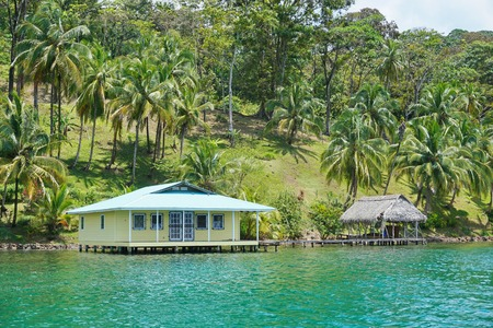waterfront property: House and hut over the water with coconut palm trees on the land, Caribbean coast of Panama, Bocas del Toro, Central America