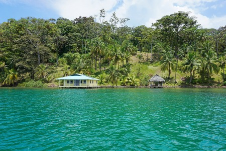 waterfront property: Waterfront property with tropical vegetation and house with hut over the water, viewed from the sea, Caribbean, Panama, Central America