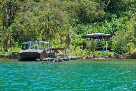 waterfront property: Tropical shore with an off-grid house and strange boat at dock on an island of the Caribbean coast of Panama, Bocas del Toro, Central America