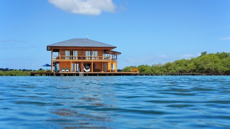 stilt house: Tropical home over the water viewed from sea surface, Caribbean, Central America Stock Photo