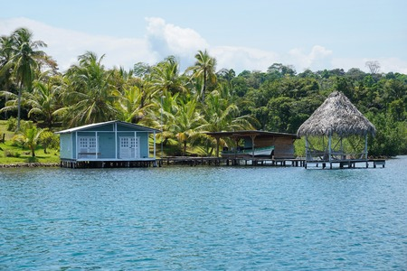waterfront property: Tropical shore with small secluded house and thatched hut over the water in Bocas del Toro, Caribbean coast of Panama, Central America