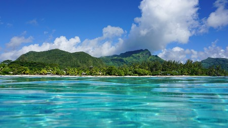 fare: Coastal landscape near the village of Fare of Huahine island, seen from the water surface in the lagoon, Pacific ocean, French Polynesia Stock Photo