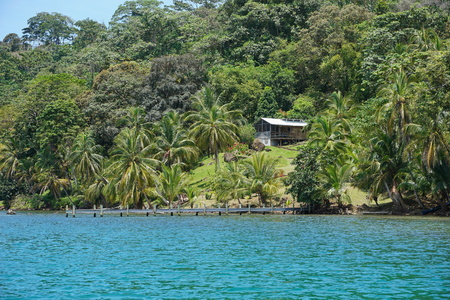 waterfront property: Coastal property with a rustic house surrounded by lush tropical forest, Bocas del Toro, Caribbean shore of Panama, Central America Stock Photo