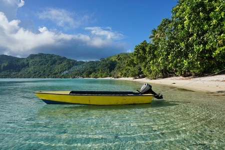 shore: Small motor boat moored on sandy shore with tropical vegetation, Avea bay, Huahine Iti island, Pacific ocean, French Polynesia