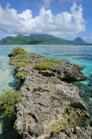 islet: Narrow reef islet with Huahine Nui island in background, Maroe bay, Pacific ocean, French Polynesia Stock Photo