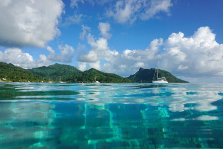 Kustlandschap van Huahine eiland in de buurt van het dorp Fare, gezien vanaf kalm water oppervlak van de lagune, Stille Oceaan, Frans-Polynesië