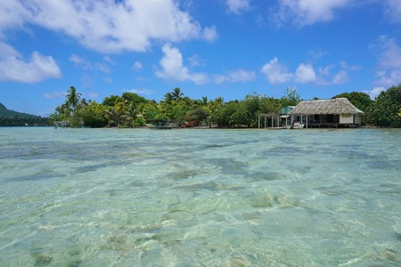 motu: Shoreline of an islet with typical Polynesian home and shallow water of the lagoon, Huahine island, Pacific ocean, French Polynesia Stock Photo