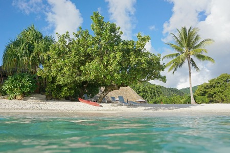 fare: Tropical shore near a resort with a kayak and lounge chairs on the beach, seen from water surface, Fare, Huahine island, south Pacific, French Polynesia
