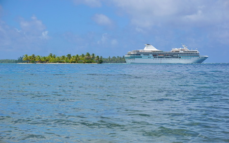 motu: Cruise ship with a tropical islet at the horizon, Huahine island, Pacific ocean, French Polynesia