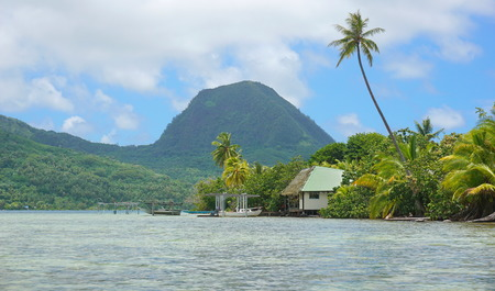motu: Shore of an islet with an house and the mount Moua Tapu in background, Huahine island, south Pacific, French Polynesia