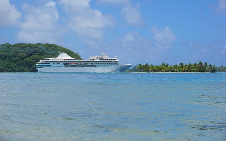 motu: Cruise ship near a tropical islet, Huahine island, Pacific ocean, French Polynesia