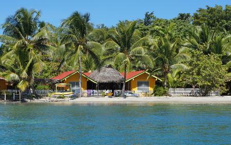 Waterfront hostel on tropical beach with coconut trees, Carenero island, Bocas del Toro, Caribbean, Central America, Panama Stock Photo