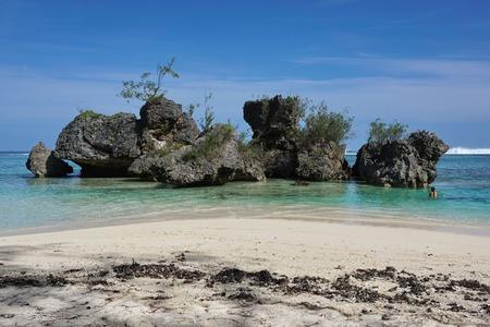 Large eroded limestone rocks in the lagoon close to sandy beach, Rurutu island, south Pacific ocean, Austral archipelago, French Polynesia Stock Photo