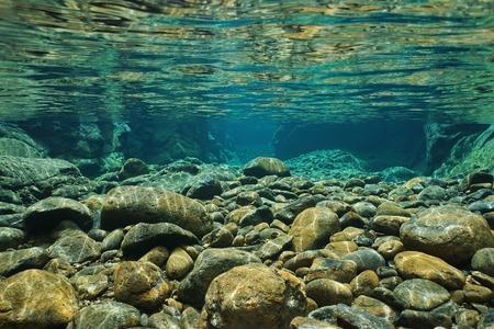 agua: Rocas bajo el agua en el cauce del río con agua dulce clara, río Dumbea, Grande Terre, Nueva Caledonia