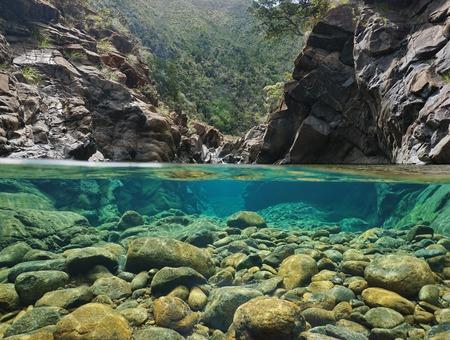 Rotsen over en onder het water dat door waterlijn in een rivier met duidelijk water, Dumbea rivier, Nieuw-Caledonië wordt verdeeld Stockfoto