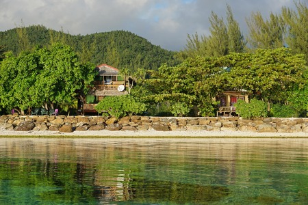 Coastal homes with green vegetation on the shore of Huahine island, Pacific ocean, Society islands, French Polynesia