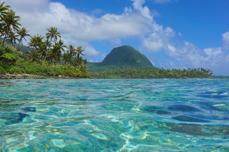 Coastal landscape of Huahine island, islet with coconut trees and the mount Moua Tapu seen from the lagoon, south Pacific ocean, French Polynesia Stock Photo