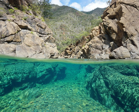 Half and half over and under the water in a river with rocks, New Caledonia, Dumbea river