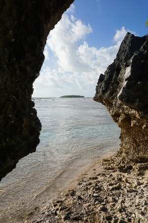 south pacific ocean: An islet in background between eroded rocks on the sea shore, atoll of Tikehau, Tuamotu archipelago, French Polynesia, south Pacific ocean Stock Photo