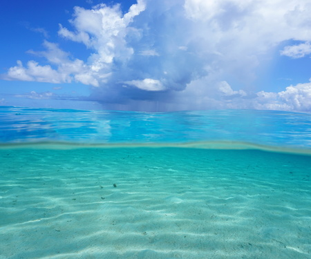 ocean and sea: Half and half, Pacific ocean seascape, shallow sandy seabed underwater with cloudy blue sky over the water, French Polynesia