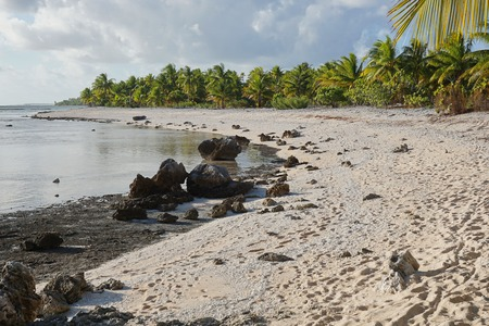 south pacific ocean: Coastal landscape, tropical sea shore with sand and rocks on the atoll of Tikehau in the Tuamotu archipelago, French Polynesia, south Pacific ocean Stock Photo