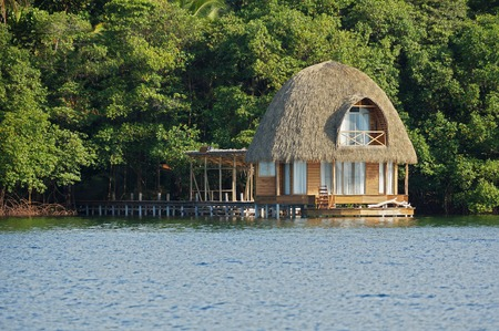 Wooden overwater bungalow with thatched roof, tropical architecture, Bocas del Toro, Caribbean sea, Central America, Panama