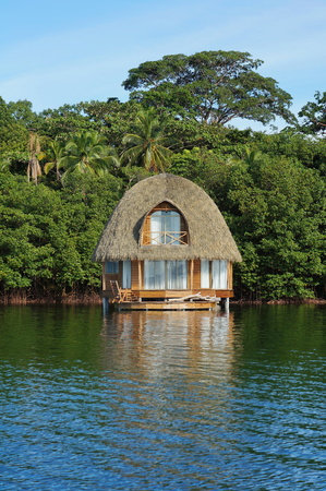 Charming overwater bungalow with thatch roof and lush tropical vegetation on the seashore, Bocas del Toro, Caribbean sea, Central America, Panama