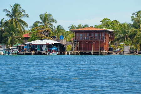 Tropical coast with a Caribbean house and small fuel station for boats, archipelago of Bocas del Toro, Carenero island, Panama Stock Photo