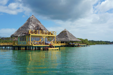 Tropical eco resort over water with thatched roof made of dried palm leaves, Caribbean sea, Bocas del Toro, Panama