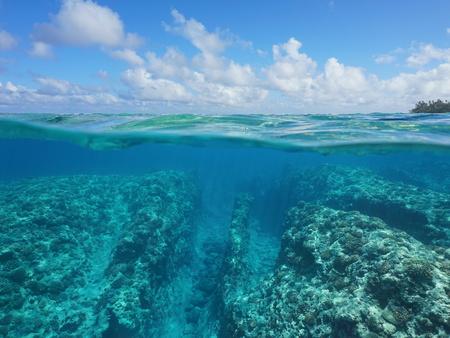 Over onder wateroppervlak, rotsige zeebodem met koraalrif onderwater en bewolkte blauwe hemel gedeeld door waterlijn, Huahine, Pacifische oceaan, Frans-Polynesië