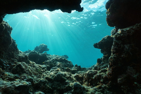 Underwater sunlight through water surface from a hole in a rocky ocean floor, natural scene, Pacific ocean, outer reef of Huahine, French Polynesia