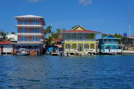 Colorful waterfront colonial houses over the sea with boats at dock, Colon island, Bocas del Toro, Caribbean coast of Panama, Central America Stock Photo