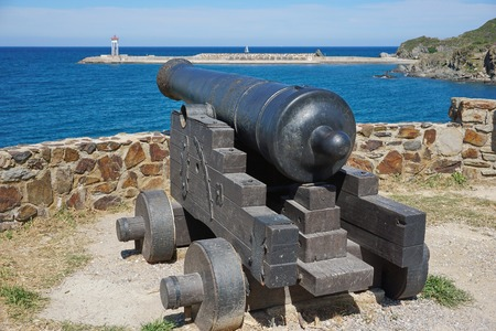 port vendres: Old iron cannon pointing at the sea in the harbor of Port-Vendres, Mediterrean, Cote Vermeille, Roussillon, Pyrenees Orientales, south of France Stock Photo