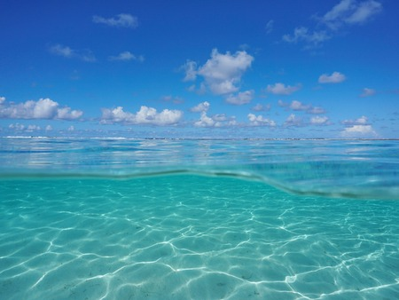Seascape over and under sea surface, tropical lagoon with cloudy blue sky and underwater a shallow sandy seabed split by waterline, Pacific ocean, Bora Bora, French Polynesia 스톡 콘텐츠