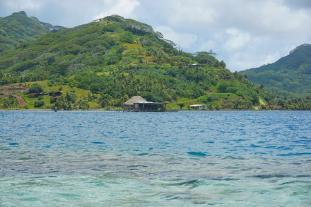 South Pacific island Huahine in French Polynesia coastline with a pearl oyster farm over water in the lagoon