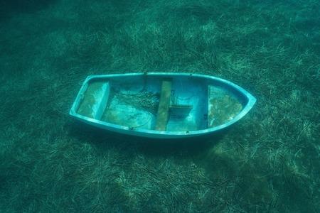 A small sunken boat underwater on the seafloor with seagrass leaves, Mediterranean sea, Catalonia, Costa Brava, Spain Stock Photo