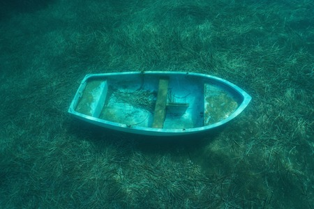 A small sunken boat underwater on the seafloor with seagrass leaves, Mediterranean sea, Catalonia, Costa Brava, Spain Archivio Fotografico