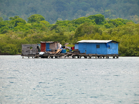 Rustic house on stilts over the water with coast and jungle in background, archipelago of Bocas del Toro, Panama, Caribbean sea, Central America
