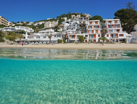 Mediterranean beachfront over and under sea surface with buildings and a sandy seabed underwater, Spain, Costa Brava, playa Almadrava, Canyelles Grosses, Roses, Girona, Catalonia Stok Fotoğraf