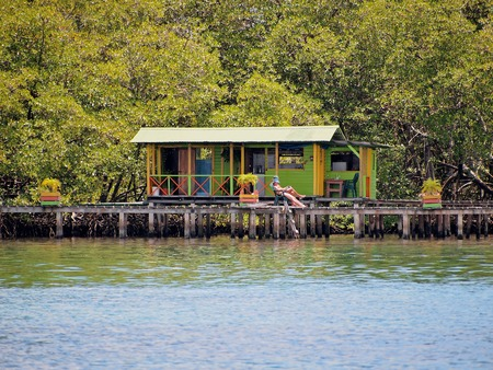 Tropical bungalow over water with people resting on the dock and luxuriant mangrove trees in background, Caribbean sea, Bocas del Toro, Panama, Central America Stock Photo