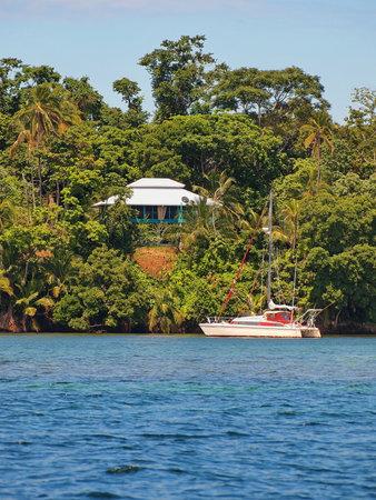 Coastal house with tropical vegetation and a sailboat anchored, Caribbean sea, Bocas del Toro, Panama, Central America
