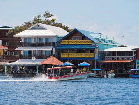 Tropical hotel restaurant over water with boat, Bocas town, Caribbean sea, Bocas del Toro, Panama