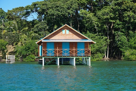 Bungalow over water with tropical vegetation in background, Caribbean sea, Bocas del Toro, Panama