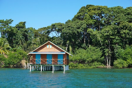 Bungalow over the sea with tropical vegetation in background, Caribbean, Bocas del Toro, Panama
