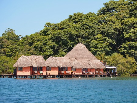 Tropical resort with thatched cabins over the water and lush vegetation in background, Caribbean sea