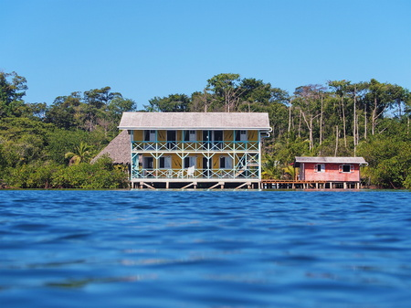 Tropical coast with a waterfront hotel and a small house over the water, Caribbean sea, Bocas del Toro, Panama, Central America Editorial