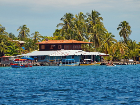 Tropical coast with caribbean houses, boats and coconut trees in Carenero island, Bocas del Toro, Panama