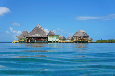 Tropical resort overwater with thatched roof viewed from water surface, Colon island, Caribbean sea, Panama